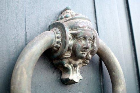 detalle de cabeza de mujer en tirador de puerta
